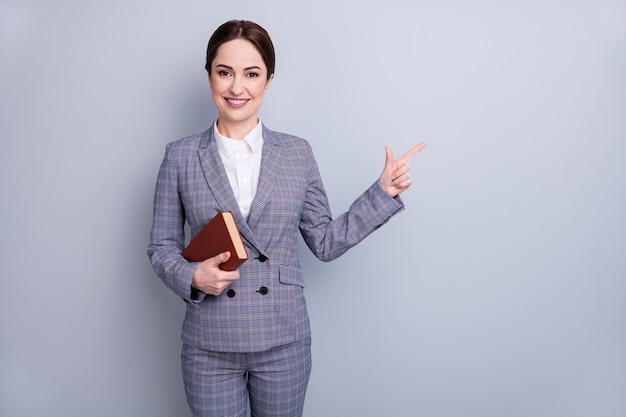 Retrato dela, ela é legal, atraente, inteligente, especialista, especialista, alegre, tutora, vestindo um terno xadrez casual segurando um livro que mostra o anúncio do espaço da cópia isolado sobre o fundo cinza pastel