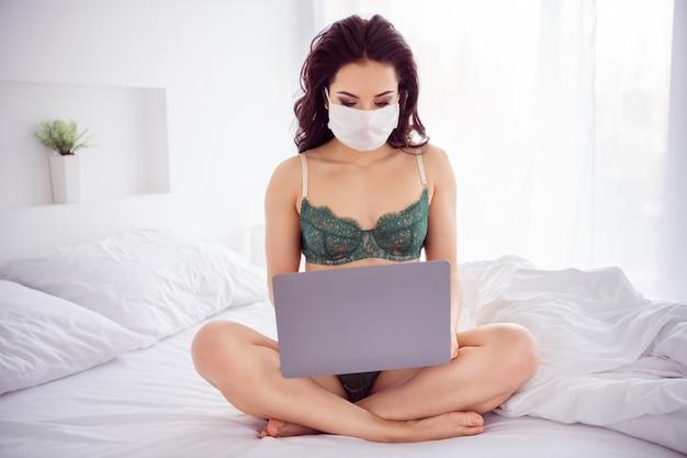 Retrato dela, ela é legal, atraente, linda, linda, nua, nua, sentada na cama, usando uma máscara de gaze, usando um laptop digital, conversando com o namorado.