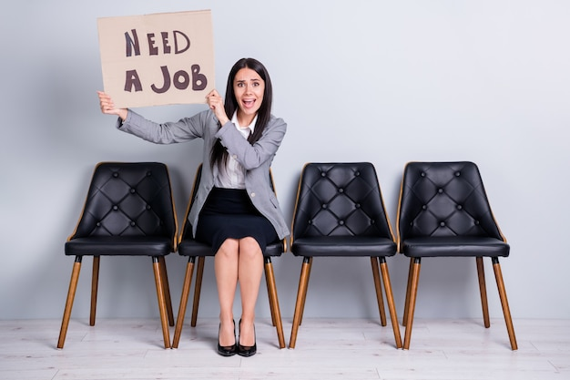 Retrato dela, ela é simpática, atraente, desesperada, despedida, gerente executiva, sentada na cadeira, segurando um cartaz em busca de emprego, gritando, ajude-me, por favor, isolado fundo de cor cinza pastel