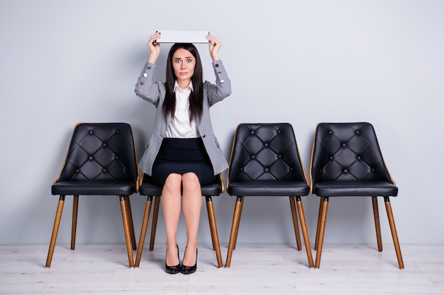 Retrato dela, ela, simpática, atraente, com medo, senhora, executivo, empresa, gerente, sentado, em, cadeira, segurando, cabeça, documento, como, telhado, seguro, esperar, reunião, isolado, pastel, cor cinza fundo