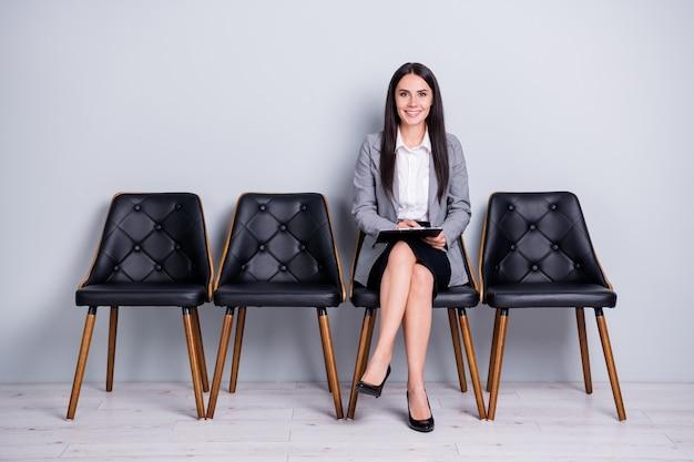 Retrato dela, ela, simpática, atraente, elegante, alegre, confiante, senhora, gerente executivo de mercado, sentado na cadeira, escrevendo o plano de estratégia anti crise isolado fundo de cor cinza pastel