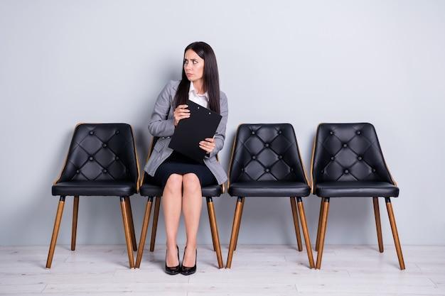 Retrato dela, ela, simpática, atraente, elegante, assustada, preocupada, senhora, gerente de vendas, corretor de imóveis, sentada na cadeira, segurando um contrato de seguro, olhando de lado isolado fundo de cor cinza pastel