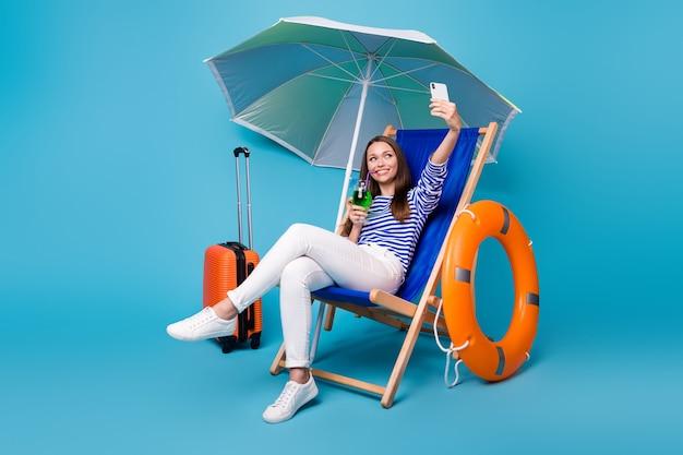 Retrato dela, ela, simpática, atraente, funky, alegre, alegre, menina, sentada na cadeira, sob o guarda-sol, bebendo, mojito, tomando selfie, lazer exótico, isolado, brilhante, vívido, brilho, vibrante, cor azul, fundo