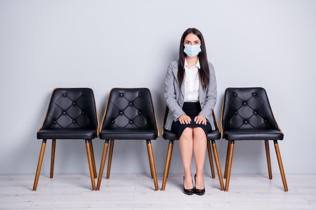 Retrato dela, ela, simpática, atraente senhora, gerente executiva, sentada na cadeira, usando máscara de gaze mers cov infecção medidas preventivas esperar reunião ceo chefe chefe isolado fundo de cor cinza pastel