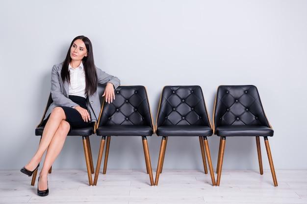 Retrato dela, mulher bonita, atraente, muito confiante, banqueiro, economista, sentado na cadeira, esperando o encontro com o parceiro do líder da empresa isolado fundo de cor cinza pastel claro
