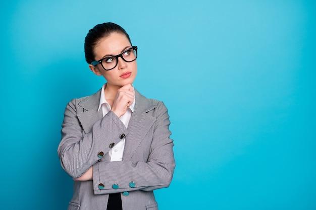 Retrato dela, mulher de negócios atraente, empregador, pensando em tocar, tomar decisões isoladas sobre fundo de cor azul brilhante