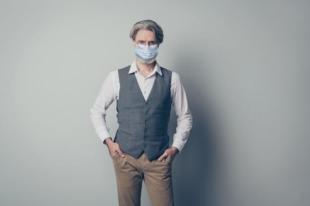 Retrato dele, bem sucedido, idoso, de cabelos grisalhos, aposentado, aposentado, usando máscara de segurança, pare de infecção cov, fique em casa, auto-isolamento, saúde, isolado, fundo cinza
