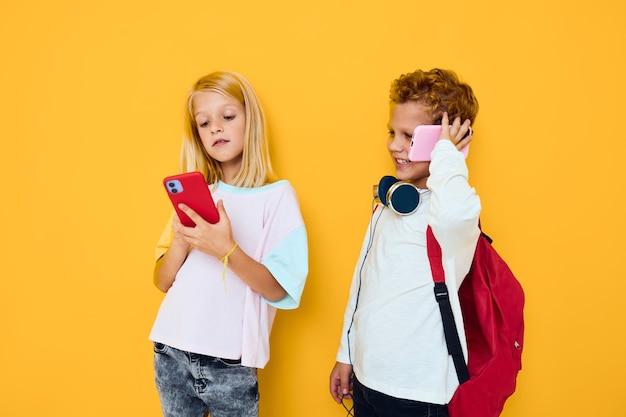 Retrato dele, ela, ela, olhando para um smartphone e jogando fundo de jogo isolado. foto de alta qualidade