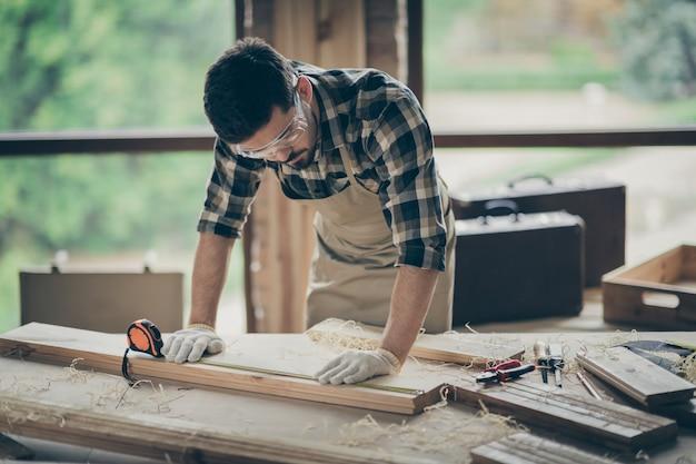Retrato dele, ele atraente, focado, concentrado, habilidoso, experiente, construtor, esculpindo madeira, criando novos móveis de armários em interiores modernos em estilo loft industrial