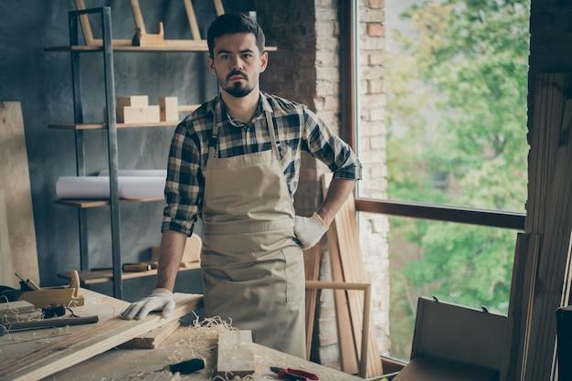 Retrato dele, ele bom atraente barbudo sério confiante bem-sucedido autônomo especialista especialista trabalhando na fabricação de estúdio em casa no interior moderno estilo loft industrial