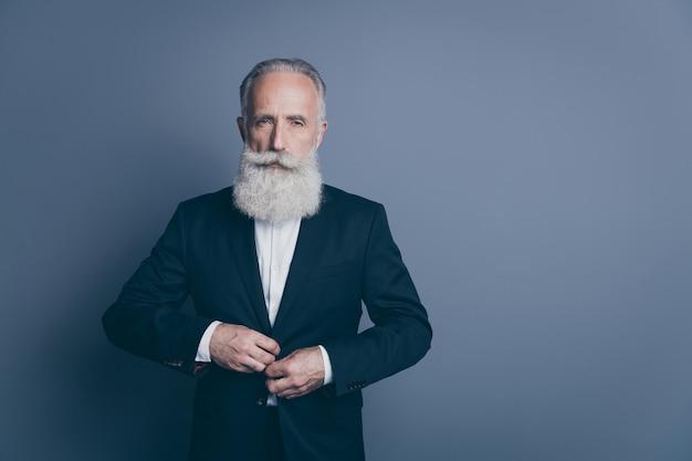 Retrato dele, ele bom atraente chique elegante homem sério de cabelos grisalhos macho dândi usando botão de fecho de smoking isolado sobre fundo cinza escuro