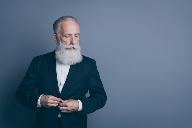 Retrato dele, ele bom, atraente, chique, elegante, sério, conteúdo, homem de cabelos grisalhos, macho, vestindo, smoking, botão, fixação, preparando-se, isolado sobre fundo cinza escuro pastel