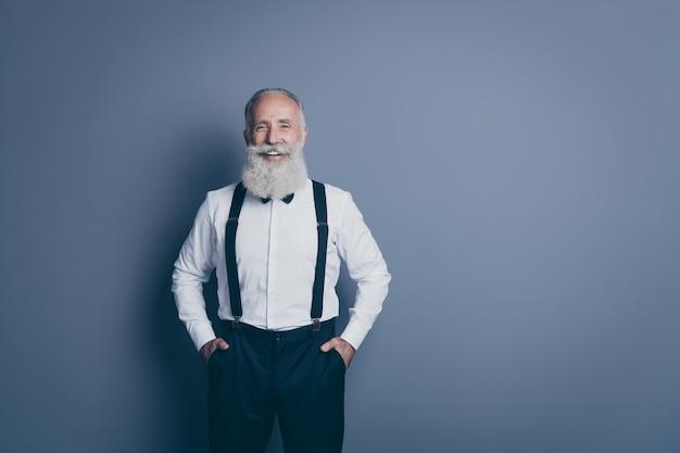 Retrato dele, ele bom atraente conteúdo elegante alegre alegre alegre homem de cabelos grisalhos de mãos dadas nos bolsos isolados sobre fundo cinza escuro pastel