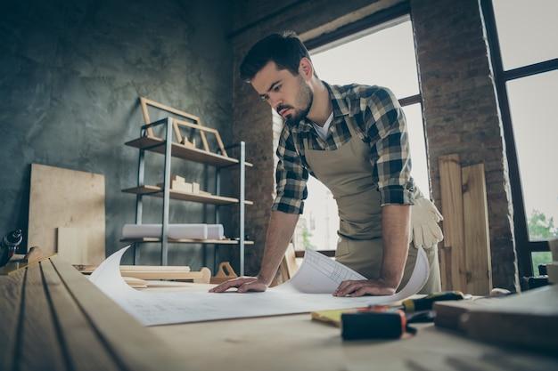 Retrato dele, ele bom atraente focado habilidoso trabalhador trabalhador, criando um plano de estratégia, desenvolvendo um projeto de construção em casa, interior moderno estilo loft industrial de tijolos dentro de casa