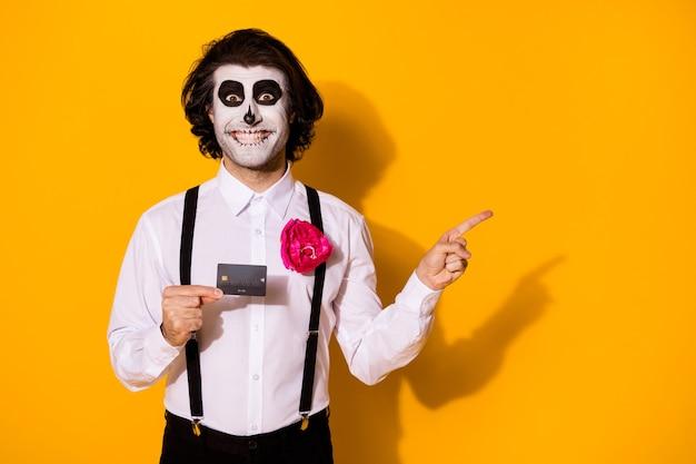 Retrato dele ele bom bonito assustador alegre alegre alegre cara segurando nas mãos cartão de plástico transferência de dinheiro mostrando cópia espaço anúncio isolado brilhante vívido brilho vibrante fundo de cor amarela