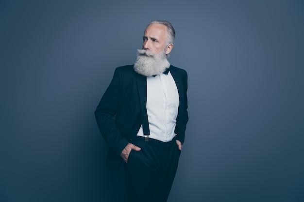 Retrato dele ele bom conteúdo atraente calmo homem sério de cabelos grisalhos olhando para o lado de mãos dadas nos bolsos isolados sobre fundo cinza escuro pastel