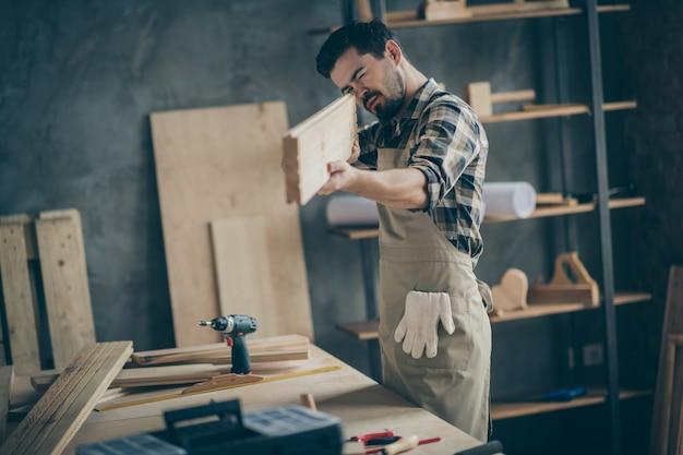 Retrato dele, ele é agradável, atraente, focado, habilidoso, trabalhador, procurando medir a prancha lisa em casa, interior moderno estilo loft industrial de tijolos dentro de casa