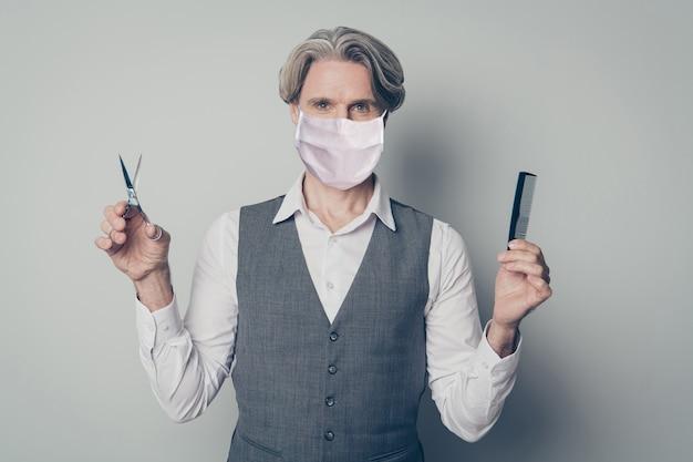 Retrato dele, ele é bom homem de cabelos grisalhos, saudável, usando máscara de segurança, escolhendo tesouras ou pente, medidas preventivas de auto-isolamento mers cov pandemia de gripe isolada cor cinza de fundo