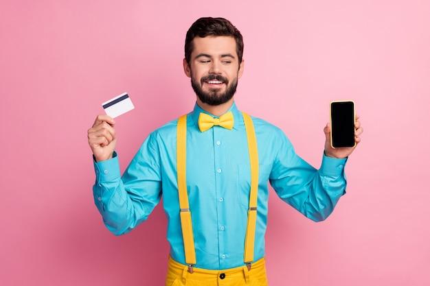 Retrato dele, ele é simpático, atraente, alegre, alegre, confiante, barbudo, vestindo uma camisa azul hortelã, segurando nas mãos o aplicativo de pagamento online do cartão do banco celular isolado sobre o fundo da cor rosa pastel
