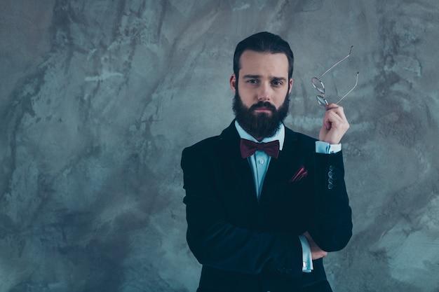 Retrato dele, ele é simpático, atraente, bem vestido, sério, experiente, focado, barbudo, vestindo um smoking, pensando isolado sobre uma parede industrial de concreto cinza