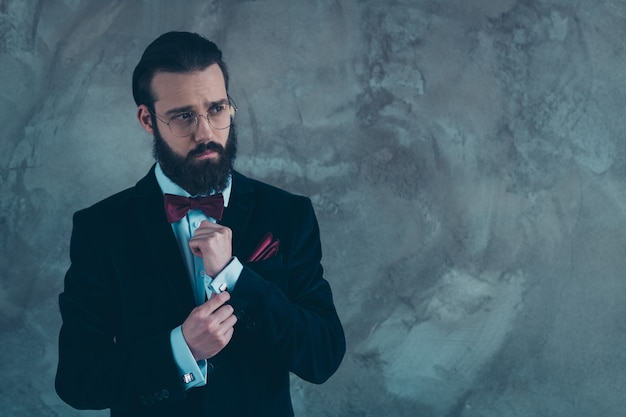 Retrato dele, ele é simpático, atraente e elegante, barbudo, vestindo um smoking consertando os punhos, preparando-se para um evento solene isolado sobre uma parede industrial de concreto cinza