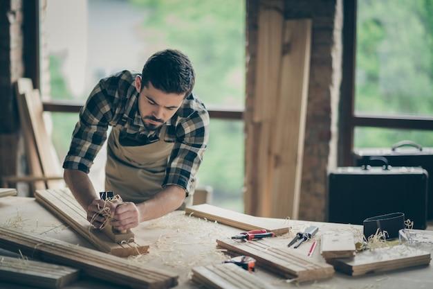 Retrato dele, ele é simpático, atraente, habilidoso, trabalhador e criativo, engenheiro autônomo, esculpindo madeira, fabricação caseira de estúdio em loft industrial moderno, interior em estilo tijolo