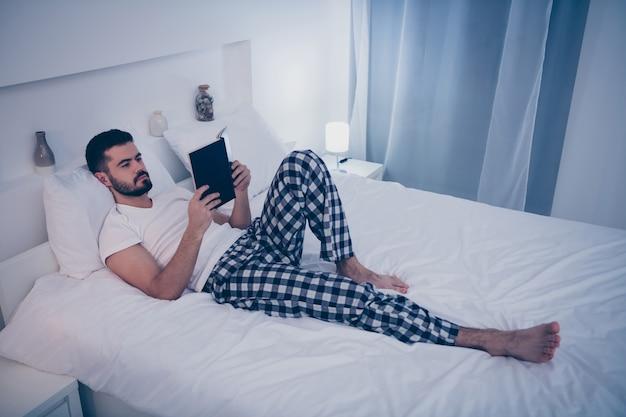 Retrato dele, ele é um cara morena atraente e atraente deitado na cama branca, descansando lendo um livro interessante à noite, tarde da noite, quarto de hotel em casa apartamento dentro