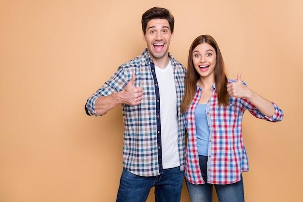 Retrato dele ele ela ela agradável atraente adorável charmoso conteúdo alegre alegre casal vestindo camisa xadrez exibindo anúncio thumbup anúncio isolado sobre fundo bege