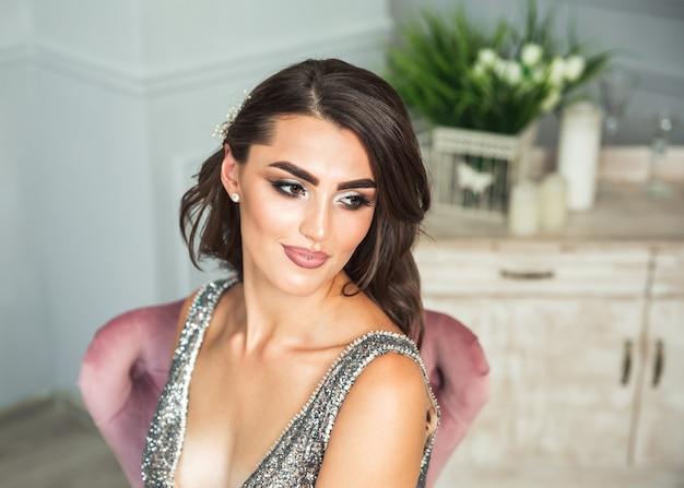 Retrato delicado de uma jovem modelo usando um vestido preto elegante e brilhante