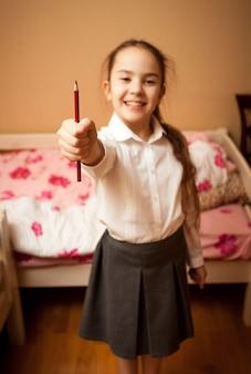 Retrato desfocado de uma colegial sorridente segurando um lápis vermelho