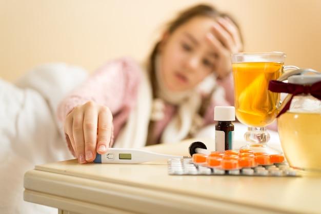 Retrato desfocado de uma doente deitada na cama a tirar o termómetro da mesa