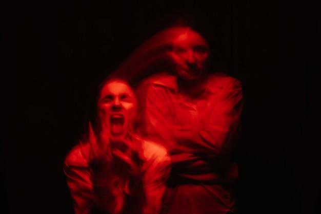 Retrato desfocado de uma menina psicopata com transtornos mentais esquizofrênicos em um fundo escuro