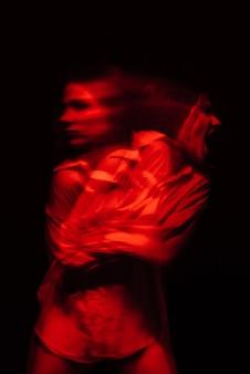 Retrato desfocado de uma mulher esquizofrênica com transtornos paranóicos e doença bipolar em um fundo escuro