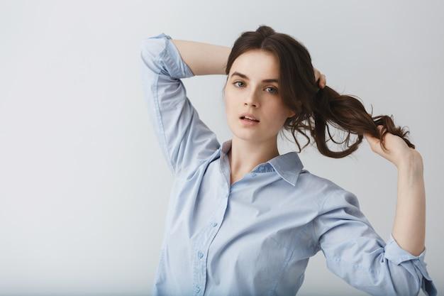 Retrato dinâmico da bela morena jovem, desenrolando o cabelo com as mãos com expressão relaxada.