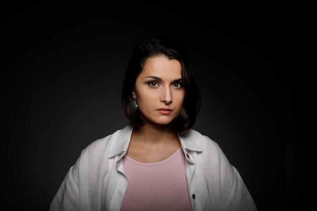 Retrato discreto de uma jovem morena séria e multiétnica de camiseta rosa e camisa branca