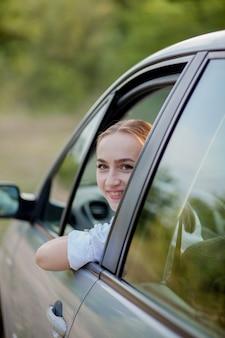 Retrato disparado através do pára-brisa de mulher bonita no carro