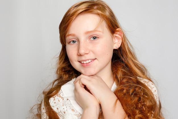 Retrato divertido de uma adorável garota ruiva em um fundo cinza. beleza, moda infantil, cosméticos, cabelos saudáveis. cabeleireiro, maquiagem, shampoo.
