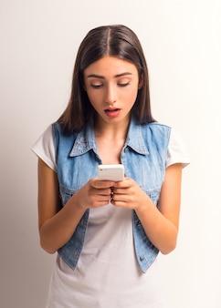 Retrato do adolescente alegre da menina que usa o telefone.