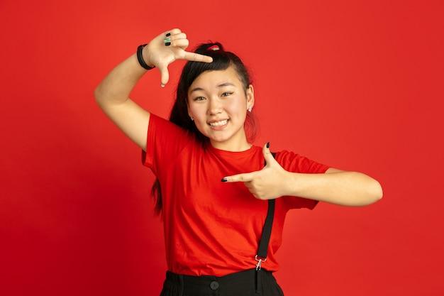 Retrato do adolescente asiático isolado no espaço vermelho. linda modelo feminino morena com cabelo comprido no estilo casual