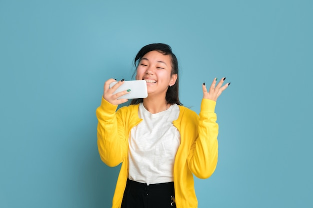 Retrato do adolescente asiático isolado no fundo azul do estúdio. bela modelo moreno feminino com cabelo comprido. conceito de emoções humanas, expressão facial, vendas, anúncio. usando o telefone, sorrindo, vitória feliz.