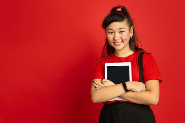 Retrato do adolescente asiático isolado no fundo vermelho do estúdio. bela modelo moreno feminino com cabelo comprido em estilo casual. conceito de emoções humanas, expressão facial, vendas, anúncio. segurando o tablet.