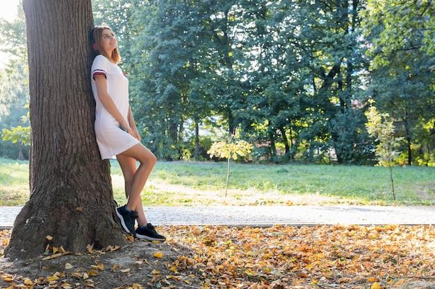 Retrato do adolescente de cabelo vermelho no vestido curto branco que escuta a música nos fones de ouvido cor-de-rosa grandes ao ar livre que inclinam-se a uma árvore.