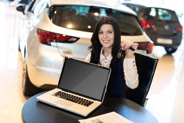 Retrato do agente de seguros smilling bonito sentado perto de carro novo