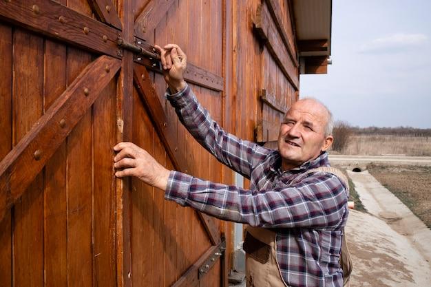 Retrato do agricultor fechando as portas do celeiro de madeira na fazenda de animais domésticos.
