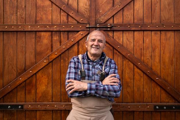 Retrato do agricultor sorridente com os braços cruzados em pé perto do celeiro de madeira ou portas do celeiro de alimentos na fazenda de animais domésticos.