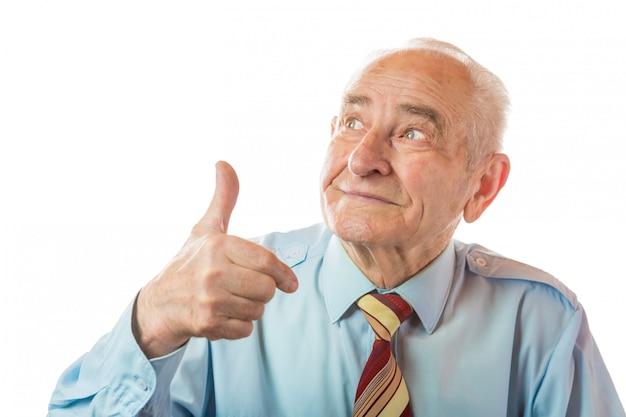 Retrato do ancião sênior europeu considerável que mostra os polegares acima do gesto isolado no fundo branco. espaço livre