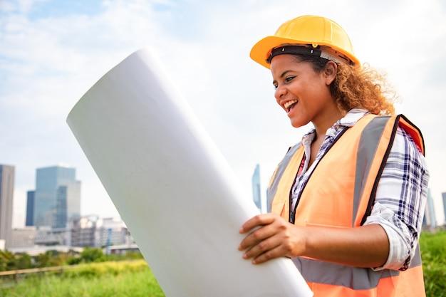 Retrato do arquiteto mulher em pé com desenhos de construção rolo de papel no parque público.