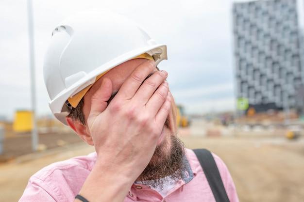 Retrato do arquiteto no trabalho com capacete com cara engraçada em um canteiro de obras, lê o plano.