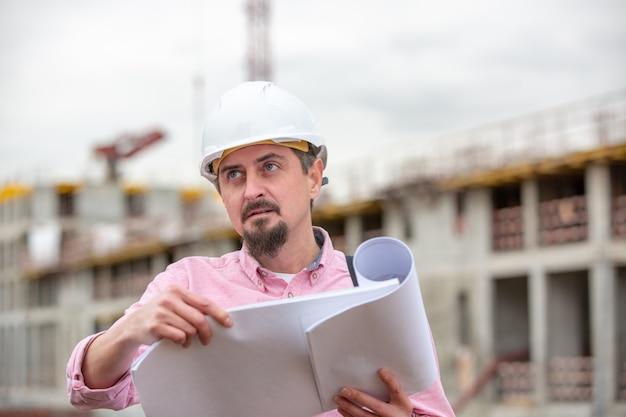 Retrato do arquiteto no trabalho com capacete em um canteiro de obras, lê o plano, projetos de papel