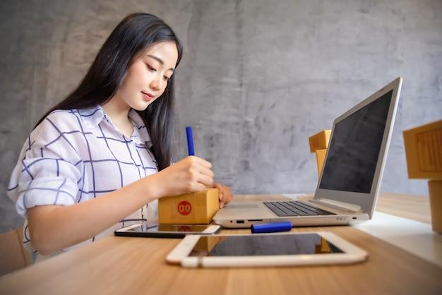 Retrato do asiático novo que trabalha a compra em linha com laptop em casa. venda on-line e conceito de entrega